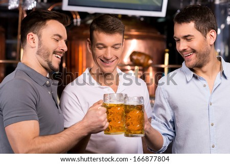 Old friends meeting. Three cheerful young men drinking beer in bar - stock photo
