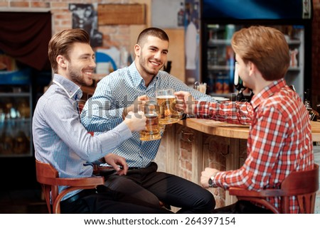 Old friends meeting. Three cheerful young men in casual wear toasting with beer  - stock photo