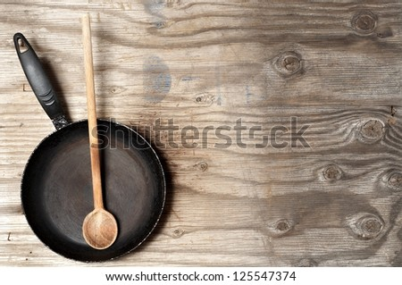 Old frying pan and spoon on wooden background - stock photo