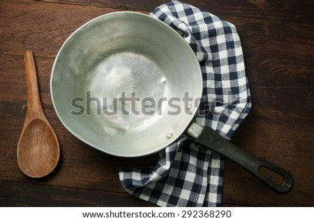 Old frying pan on wooden background. - stock photo