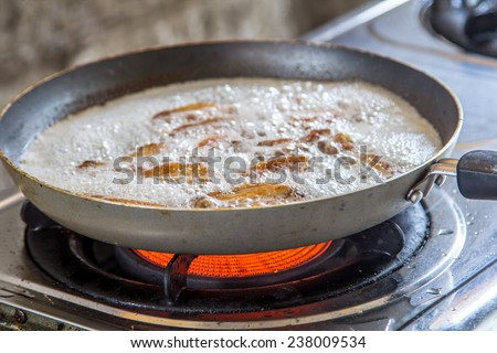 old frying pan with boiling oil on the stove. - stock photo