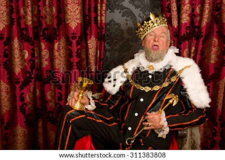 Old funny king getting drunk holding a golden goblet - stock photo