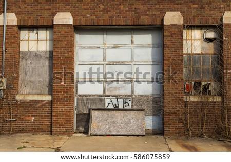 Old Garage Door And Broken Windows In Small Midwest Town.
