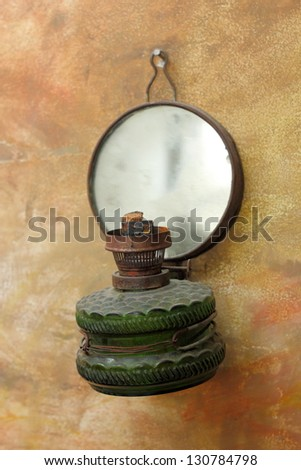 old gas lamp hanging on a painted wall as decorative object - stock photo