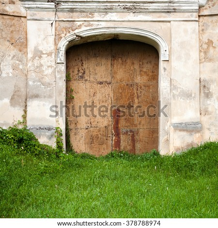 Old gates in a abandoned plaster wall - stock photo