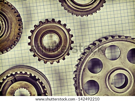 Old gears on graph paper - stock photo