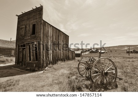 Old ghost town with wagon wheel and building in an old country town - stock photo