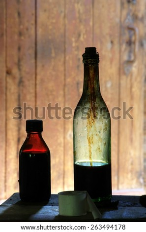 Old glass bottles on the table in old, abandoned farm house in Southern Finland.