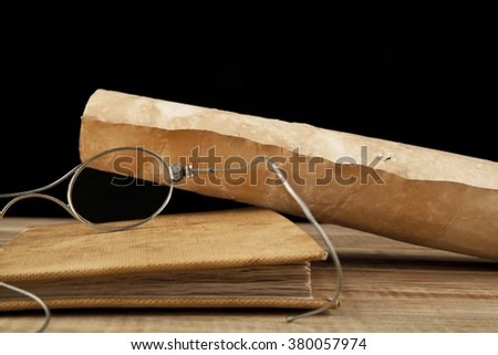 Old glasses and old books on black background - stock photo