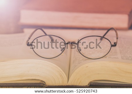 Old glasses on vintage book with lens flare technician