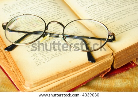 Old glasses over a vintage book of law - stock photo