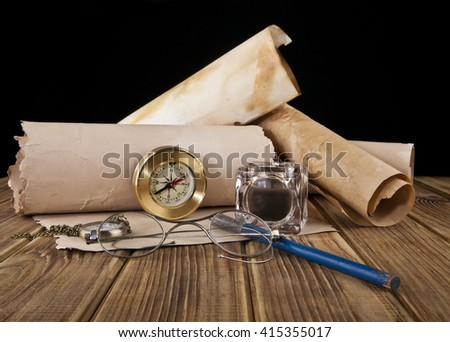 old glasses, paper, pen, clock and compass on black background