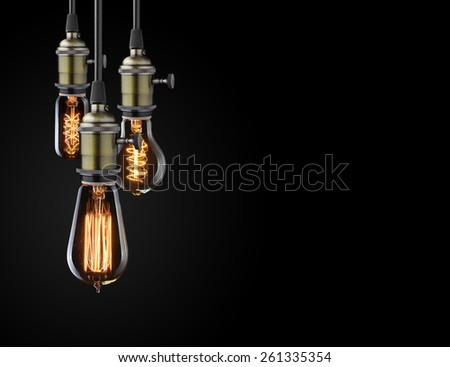 Old glowing light bulbs on black background - stock photo