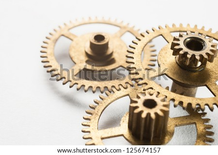 old gold clock gear on white background