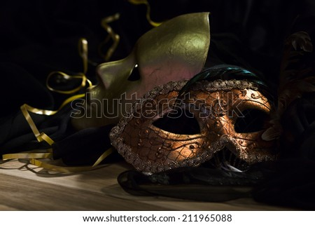 Old gold Venetian masks on a wooden table