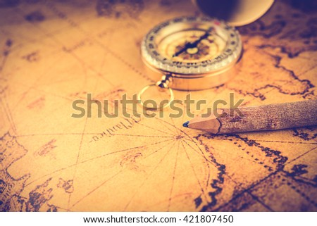 Old  gold vintage compass and pencil on vintage map