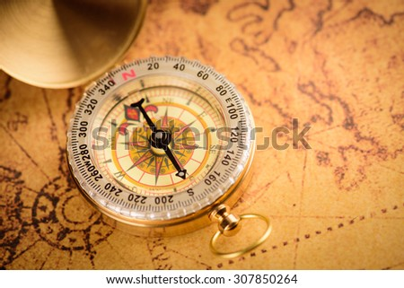 Old  gold vintage compass on vintage map:Heading south - stock photo