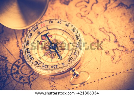 Old  gold vintage compass on vintage map:Heading south ,vintage tone style - stock photo