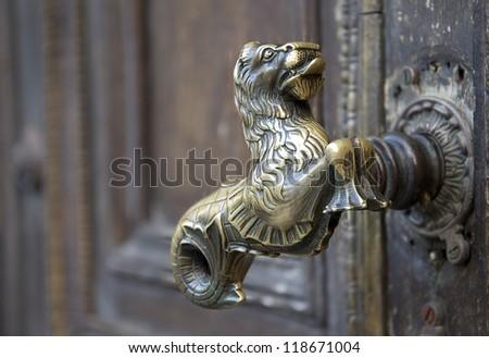 Old golden door handle unique on a wooden door - stock photo