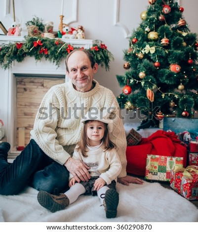 Old grandfather and granddaughter with toy horse near Christmas tree - stock photo