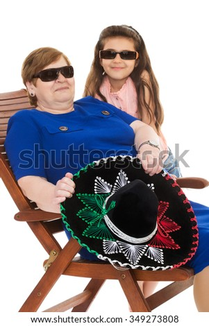 Old grandma along with his beloved granddaughter sunbathing on the lounger. Grandmother is holding a big Mexican hat , sombrero. The eyes of the grandmother and her granddaughter dark sunglasses - - stock photo