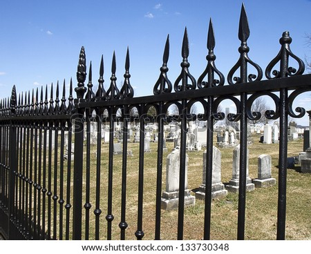 Old graves view through rod iron fence - stock photo
