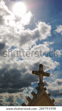 Old gravestone cross at French cemetery and sun rays glow through the clouds.  - stock photo