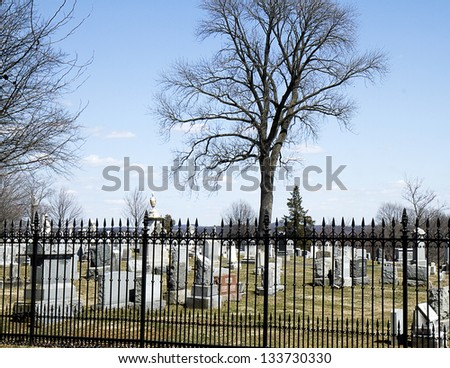 Old graveyard with rod-iron fence surrounding it - stock photo