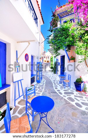Old greek town, narrow streets, white walls, blue furniture and beautiful bougainvillea - stock photo