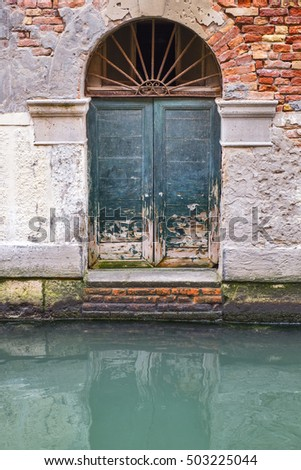 Old green door at a Venetian canal. Venice, Italy.