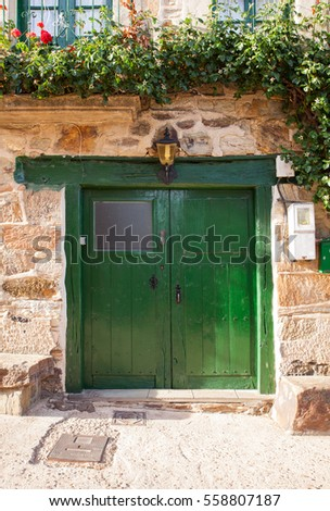Old green door of a poor Spanish house
