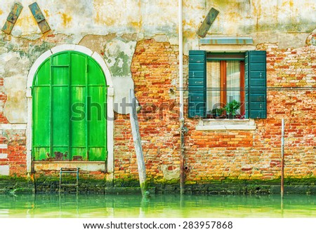 Old green iron door over a canal in Venice, Italy. - stock photo