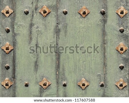 Old green painted wooden door fragment framed with rusty rivets background