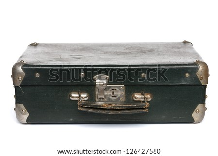 Old green suitcase with metal corners lying on the floor, isolated on white background