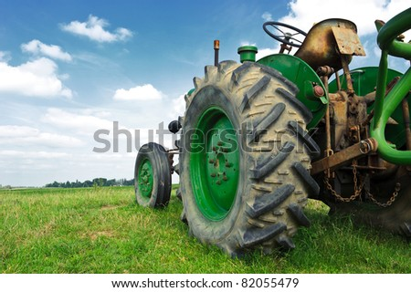 Old green tractor in the field with a cloudy sky - stock photo