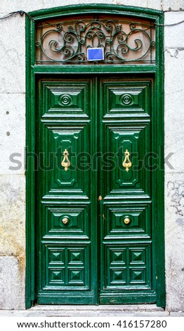 Old green wooden entrance door of house in Madrid,Spain - stock photo