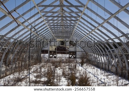 Old greenhouse structure with snow