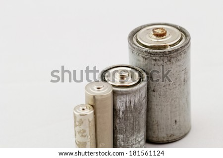 Old grey batteries on white background (aa, aaa, b, c) - stock photo