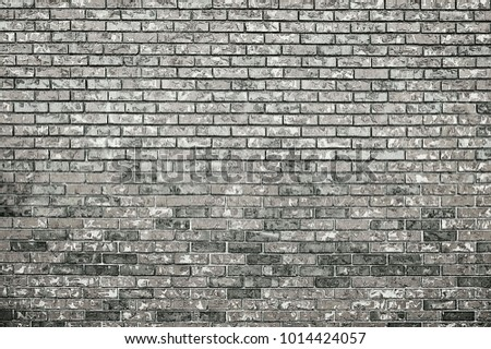 Old grey brick wall background texture close up