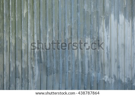Old grey gofferd metal fence with big white paint spots. Retro background - aged steel surface.