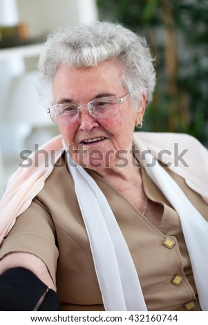 Old grey hair woman measuring her blood pressure at home - stock photo