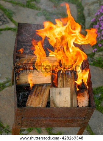 Old grill with the burning firewood and charcoal - stock photo