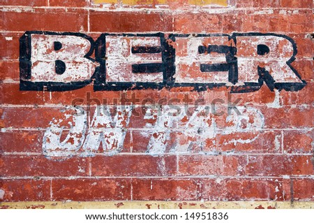 """Old grunge brick wall with inscription """"BEER ON TAP"""" - stock photo"""
