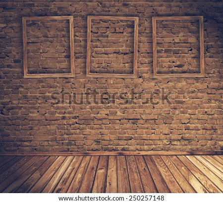 old grunge interior with blank frames against wall, retro filtered, instagram style - stock photo