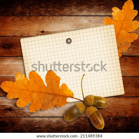 Old grunge paper with autumn oak leaves and acorns on the wooden background - stock photo