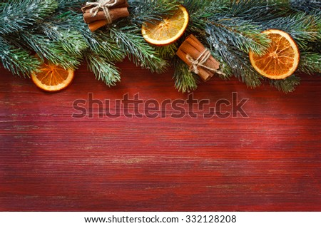 Old grunge red wooden board with Christmas border and spices. Christmas card with place for text. - stock photo