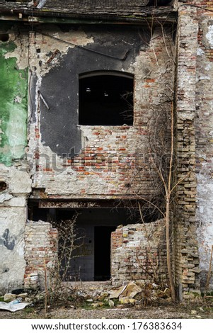Old grungy building with black window and destroyed entrance - stock photo