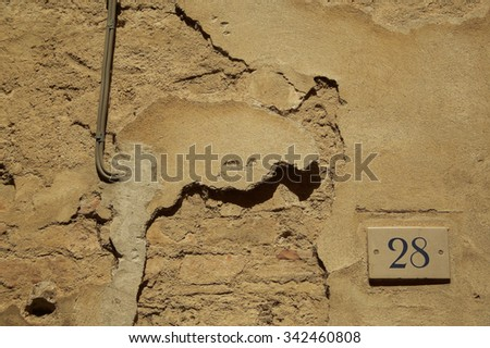 Old grungy cement brick wall with number 28 (twenty eight) - stock photo