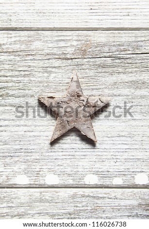 Old grungy Christmas star centred vertically on weathered planks with woodgrain and copyspace - stock photo