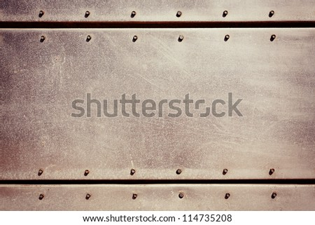 Old grungy, dirty and scratched metal plate with screws - stock photo